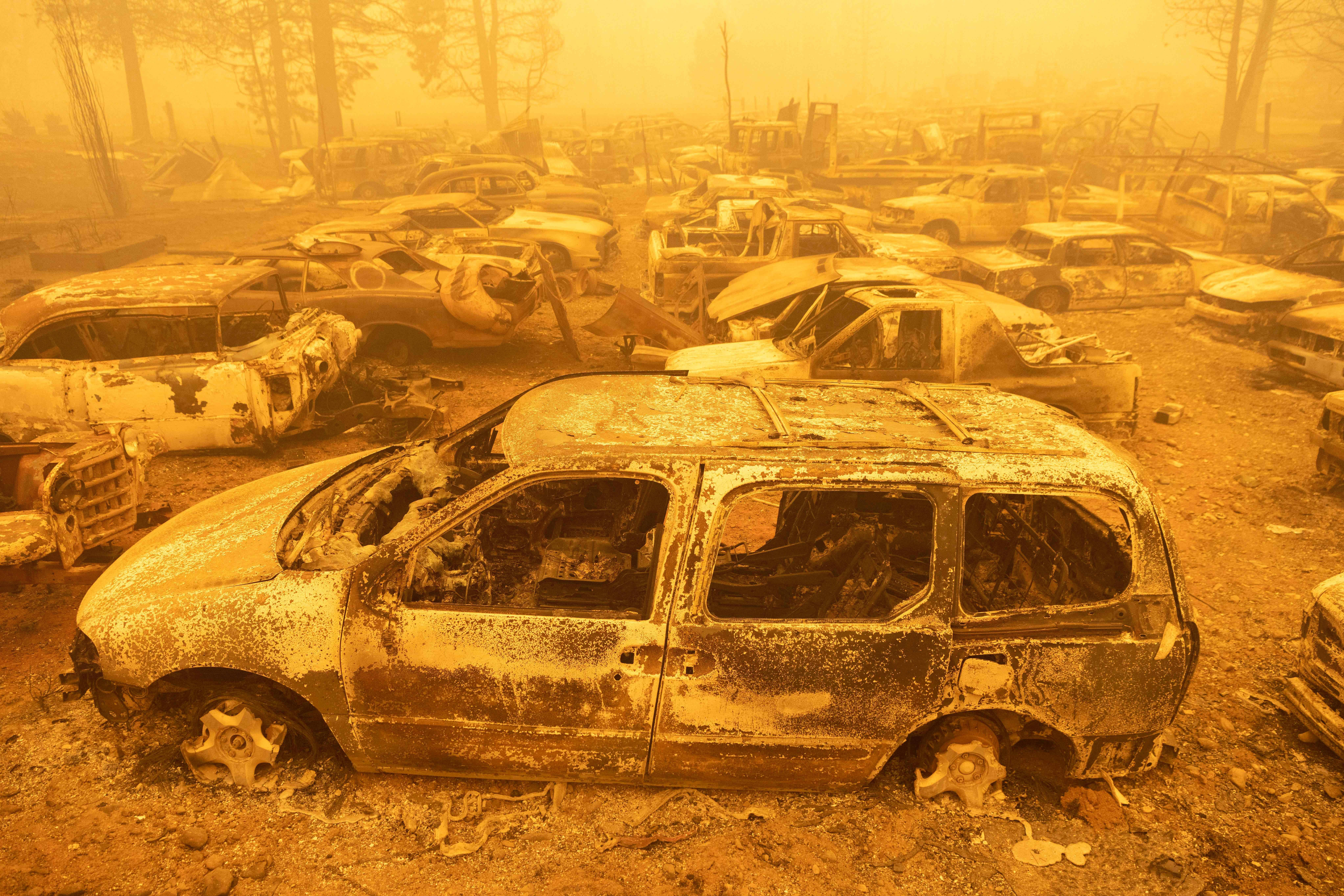 Dozens of burned vehicles rest in heavy smoke during the Dixie fire in Greenville, California on August 6, 2021.