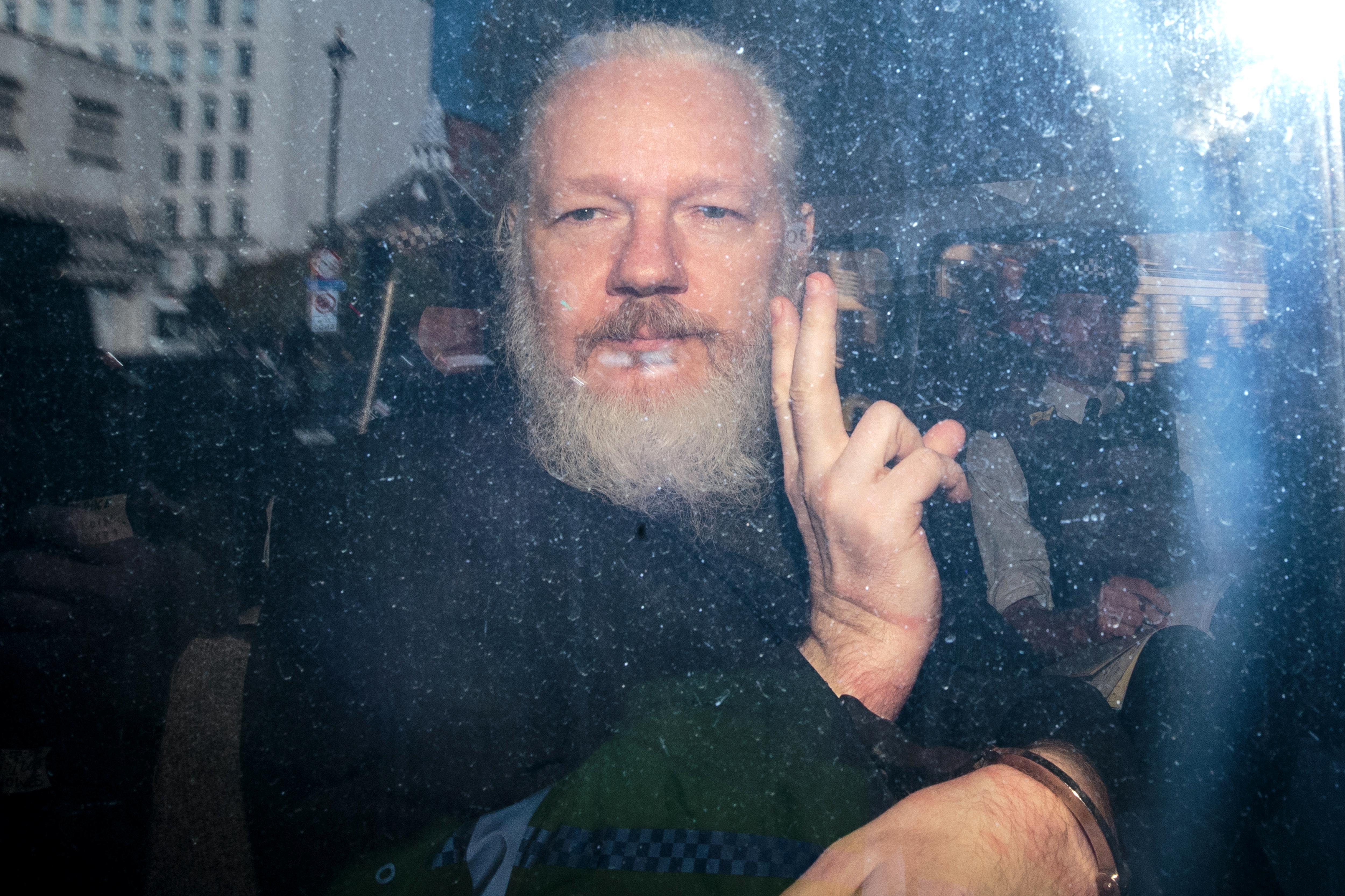 Julian Assange gestures to the media from inside a police vehicle.