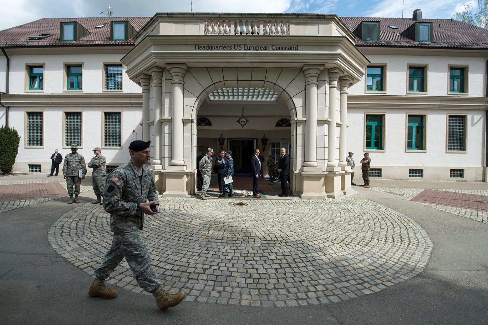 Members of the U.S. Armed Forces walk past a headquarters in Germany.