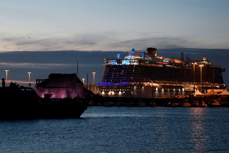 A large cruise ship with colorful lights is docked on the water as the sun sets.