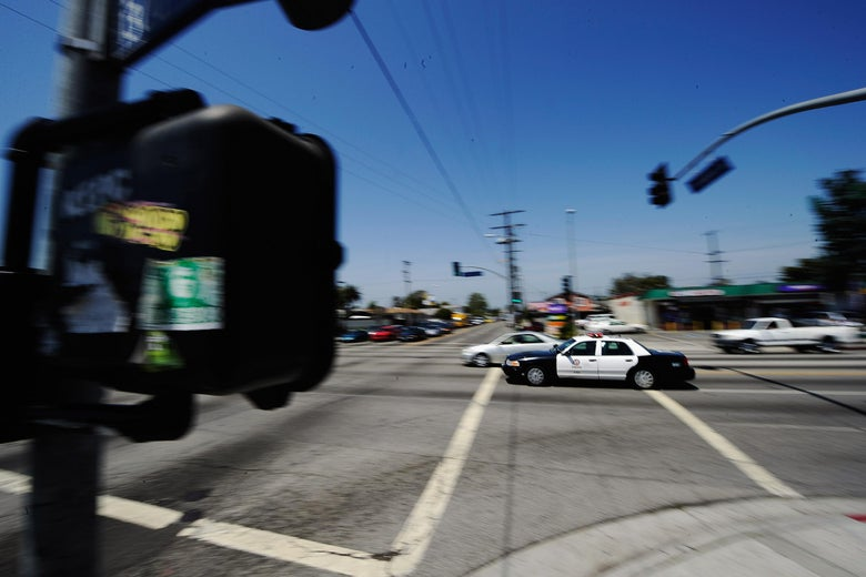 A Los Angeles Police Department car with lights and sirens going rushes through an intersection.