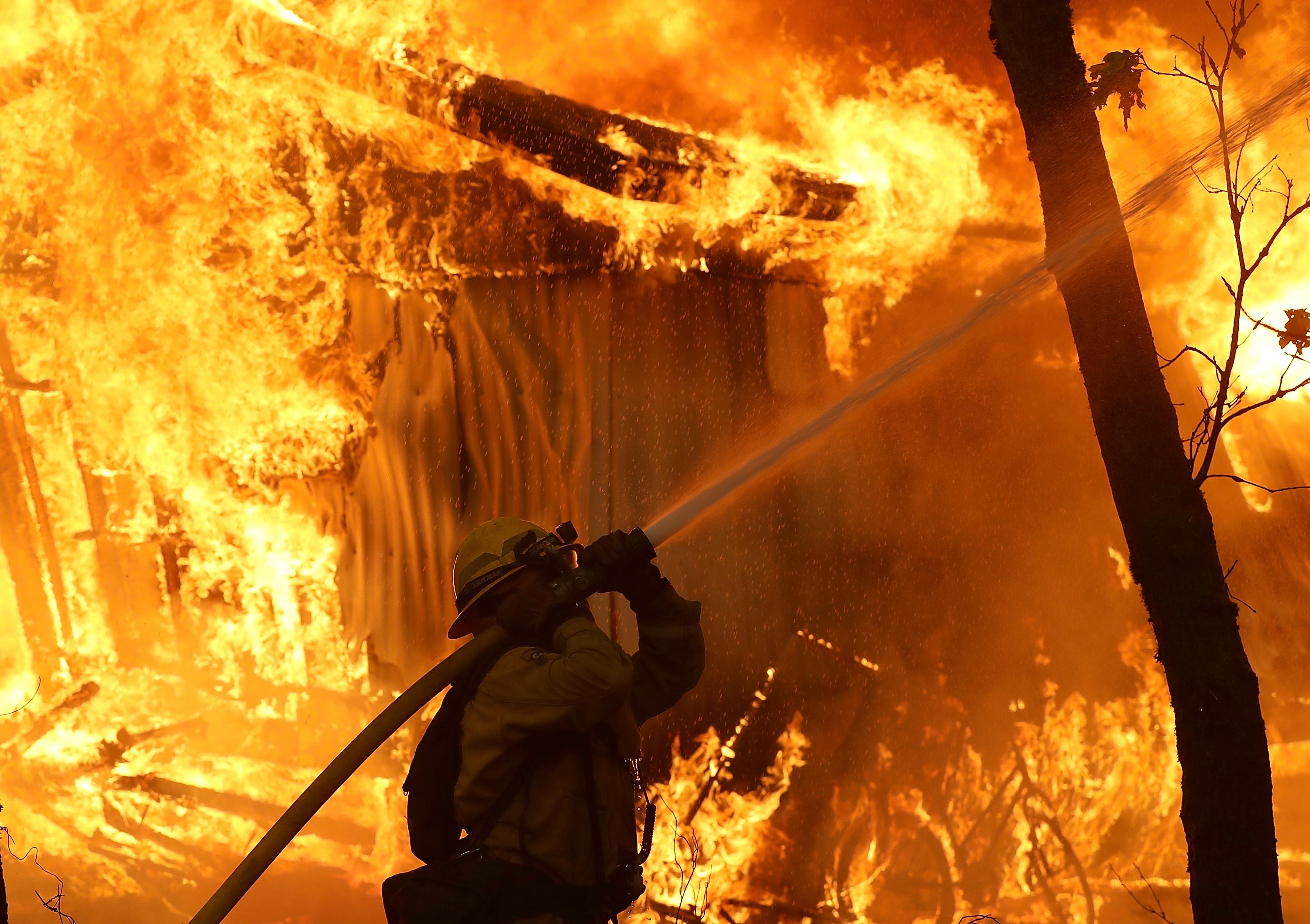 A firefighter uses a hose in the midst of a blaze.