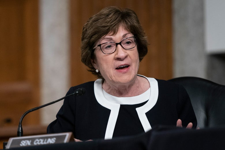 Susan Collins sits at a desk and speaks into a microphone.