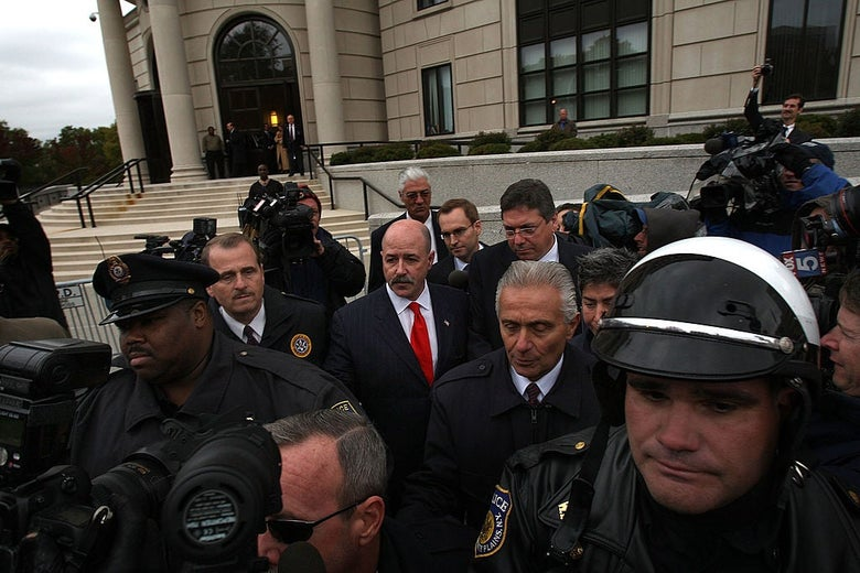 Bernard Kerik, wearing a black suit with a red tie, walks away from a set of courthouse steps while surrounded by police officers and cameras.