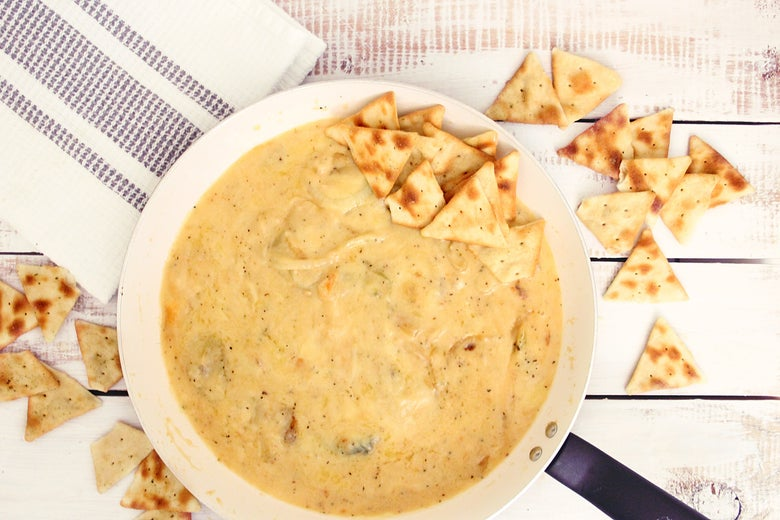 A bowl of creamy dip with some crackers around it.