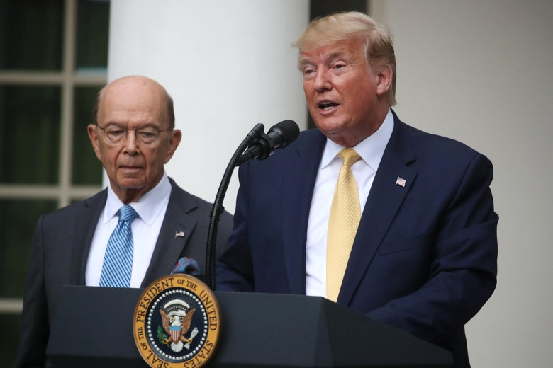Trump speaks at a lectern while Wilbur Ross stands next to him.