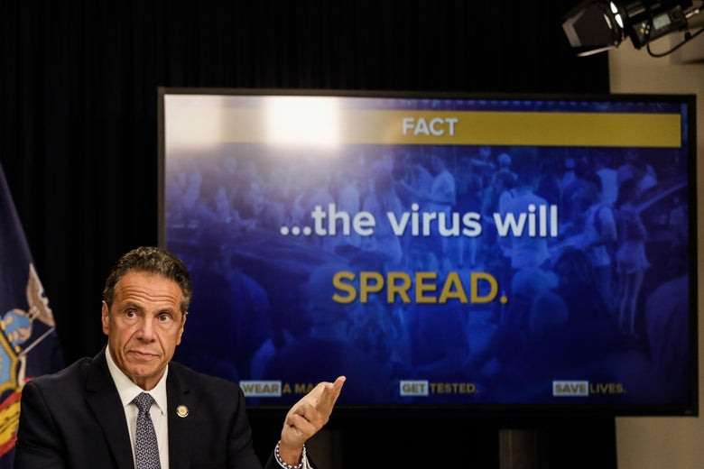 "Andrew Cuomo gestures at a screen that says ""the virus will SPREAD."""