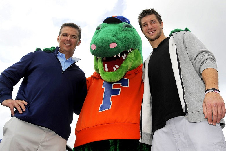 Urban Meyer, an alligator mascot, and Tim Tebow pose with their arms around one another.