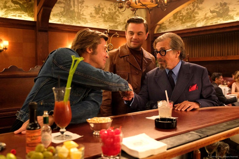In a scene from the movie, Brad Pitt and Al Pacino are seated at a bar, shaking hands, as Leonardo DiCaprio looks on.