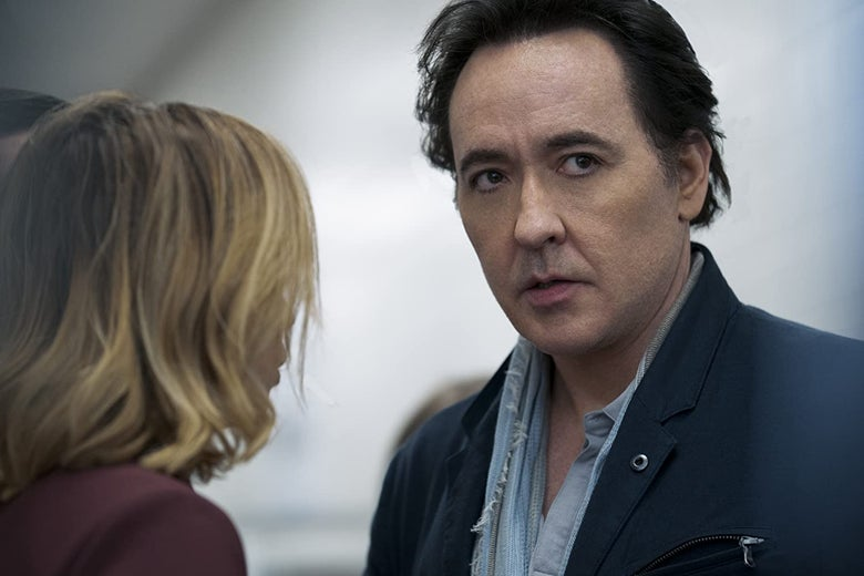 John Cusack is seen standing with a woman in a still from Amazon's Utopia.