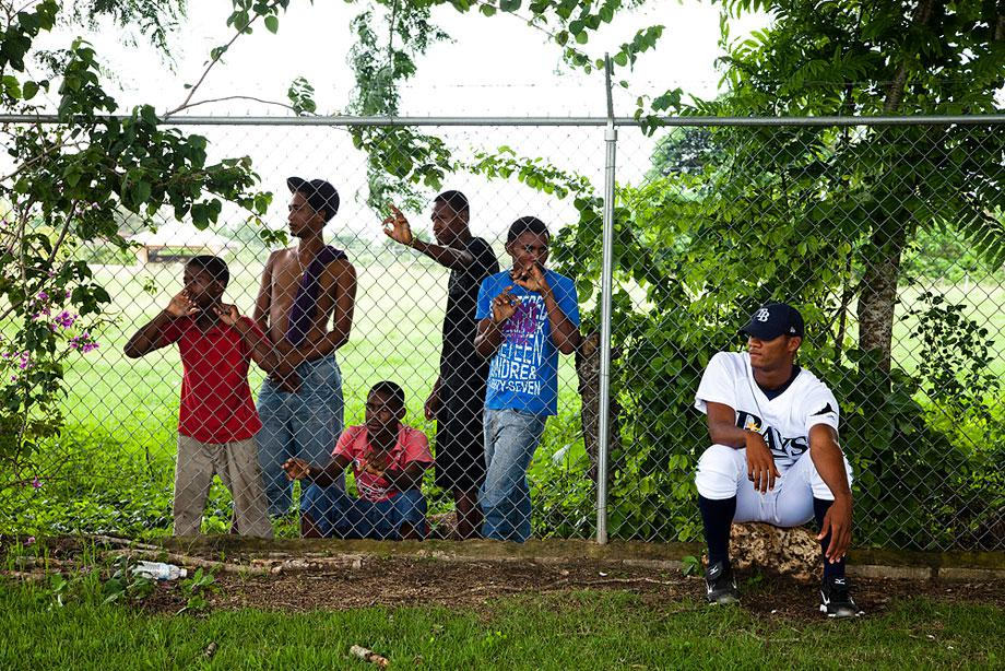 BOCA CHICA, DOMINICAN REPUBLIC. A professional player waits for foul balls near the fence line that separates the local kids. Most young boys dream of becoming a professional player where signing bonuses often exceed six figures.