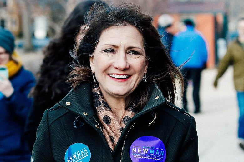 Newman smiles while walking toward the camera in a green coat decorated with campaign stickers.