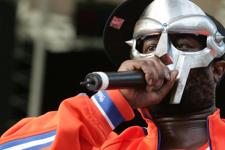 MF DOOM raises a mic and dons a Knicks Jersey, his face hidden behind his metal mask.