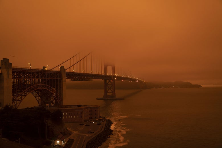 Cars drive along the Golden Gate Bridge under an orange smoke filled sky at midday in San Francisco in September.