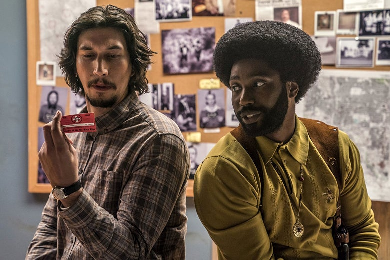 In a scene from BlacKkKlansman, Detective Flip Zimmerman (Adam Driver) holds a Ku Klux Klan membership card while Detective Ron Stallworth looks on.