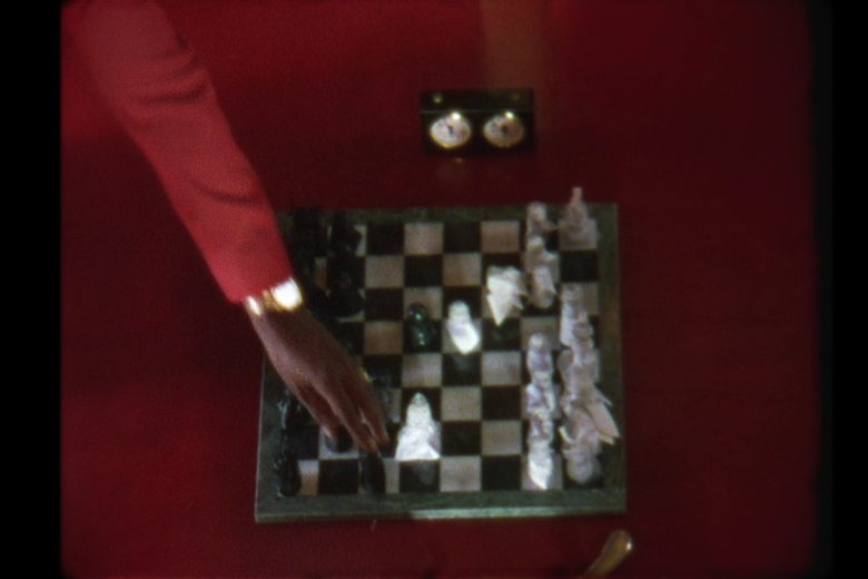 Jay-Z's hand moves a pawn on a chessboard.