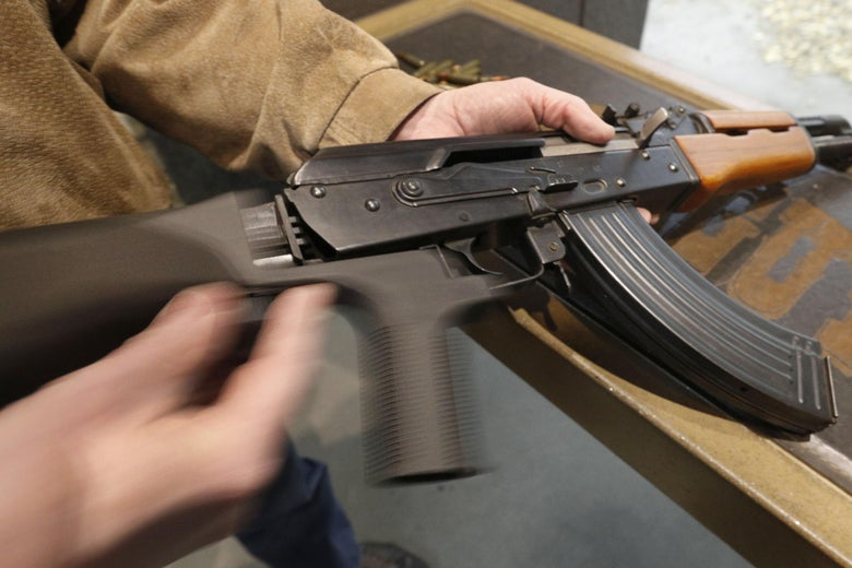 A bump stock is installed on a weapon in Orem, Utah. The device is now illegal throughout the United States.