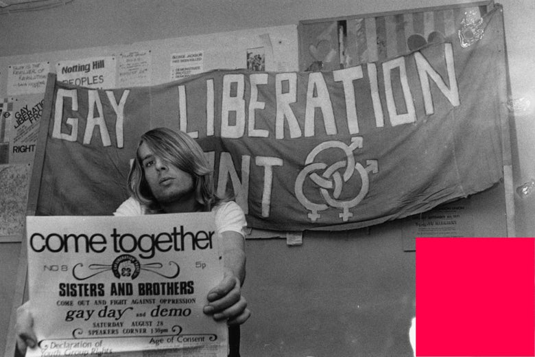 A member of the Gay Liberation Front holding a poster and under a banner.
