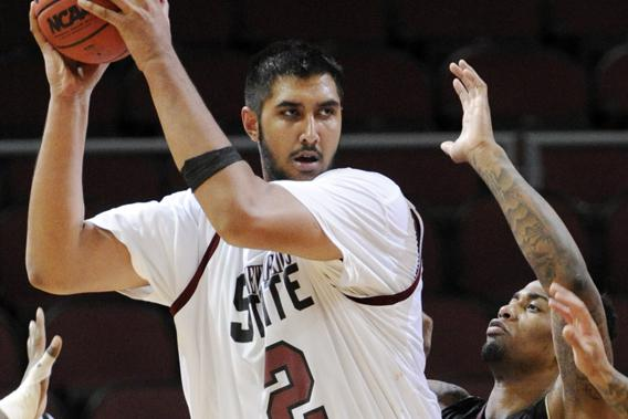 New Mexico State's Sim Bhullar looks to pass as Texas State's Joel Wright guards during the second half of a Western Athletic Conference tournament NCAA college basketball game, Friday, March 15, 2013 in Las Vegas.