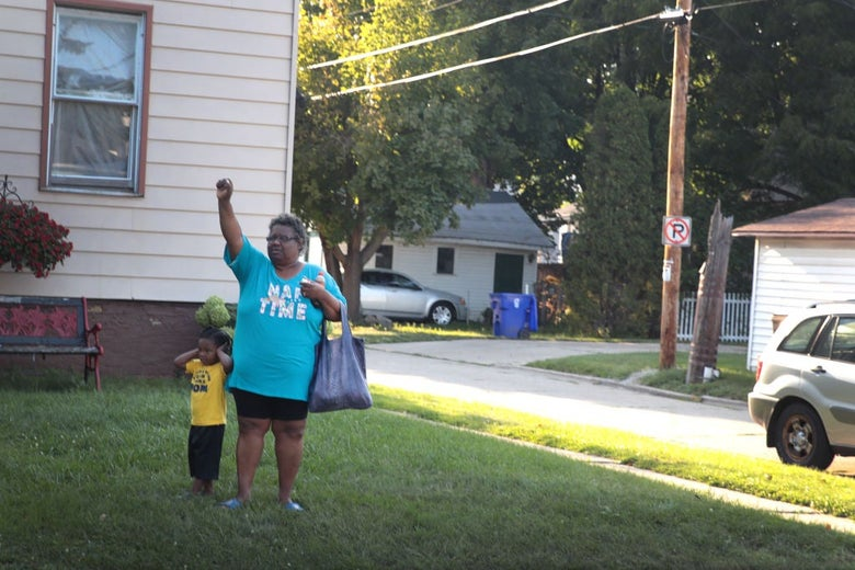 A Black woman standing in the front yard of a house with a toddler holds her right hand up in a fist.
