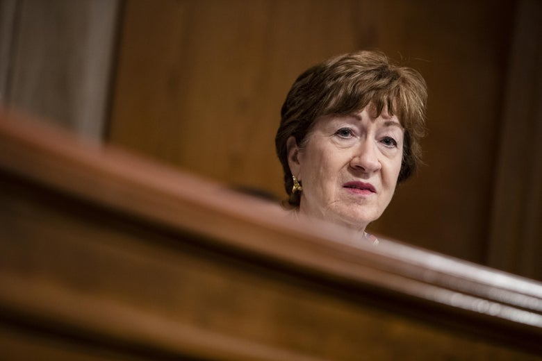 Susan Collins' head, wearing a solemn expression, peeks out above a wooden dais.