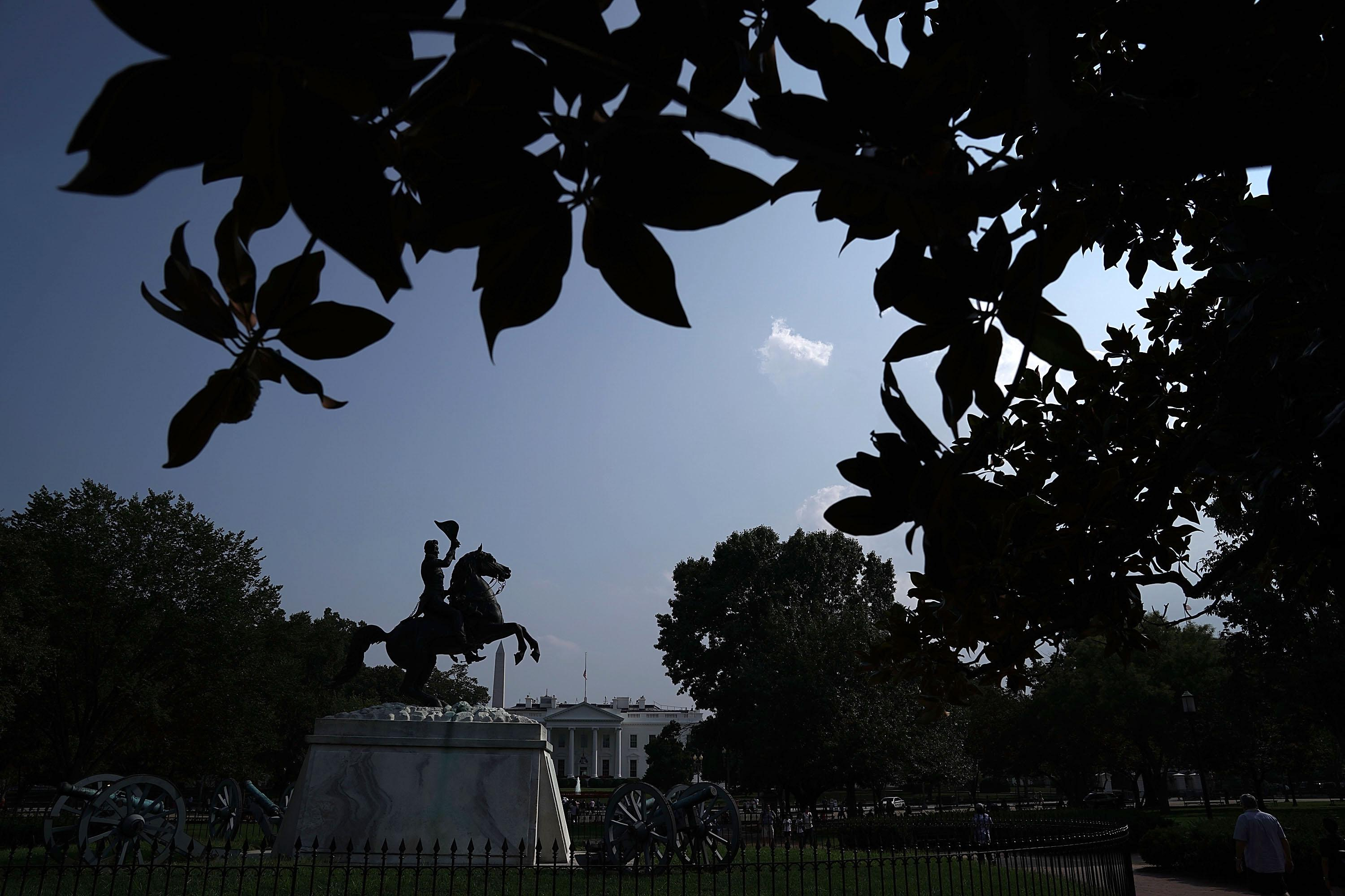 Seen behind a statue of Andrew Jackson, the American flag at the White House flies at half-staff on Monday afternoon.