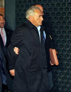 IMF head Dominique Strauss-Kahn is taken out of a police station in New York. Click image to expand.