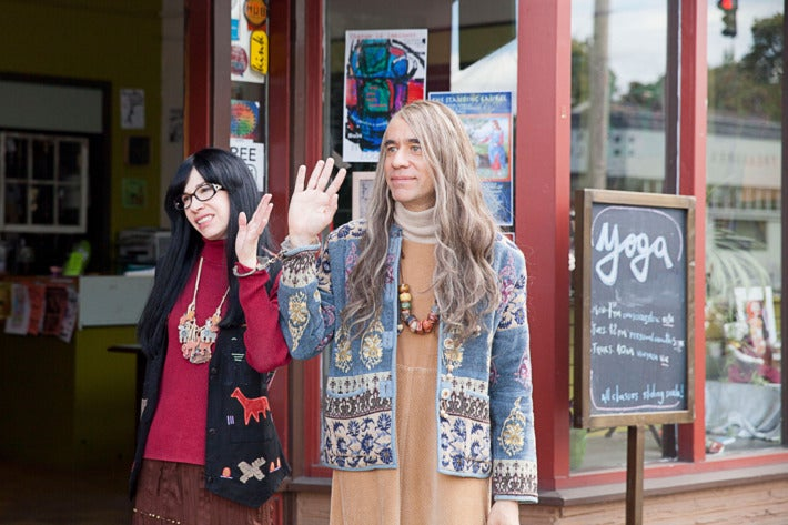 """Armisen and Brownstein, in character as co-owners of the Women and Women First bookstore, blandly wave to someone off-camera. They were stereotypical, dowdy """"feminist"""" outfits--baggy dresses, long hair, folk art-esque jewelry."""