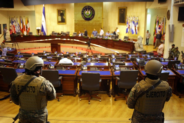 Armed soldiers stand inside the parliament building with desks and political leaders in the background.