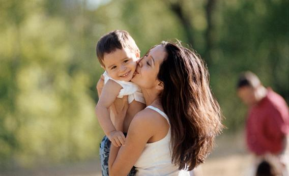 Mother holding and kissing her son outdoors.