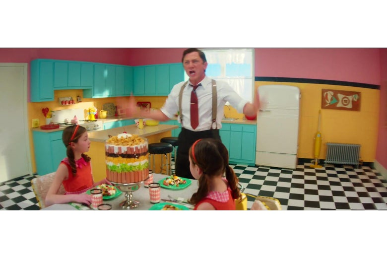 Daniel Craig stands in a pastel-colored kitchen with a checkerboard floor, yelling. The lens used to photograph him has distorted to the floors and walls behind him.