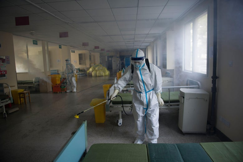 A worker wears a protective suit as he disinfects a hospital room.