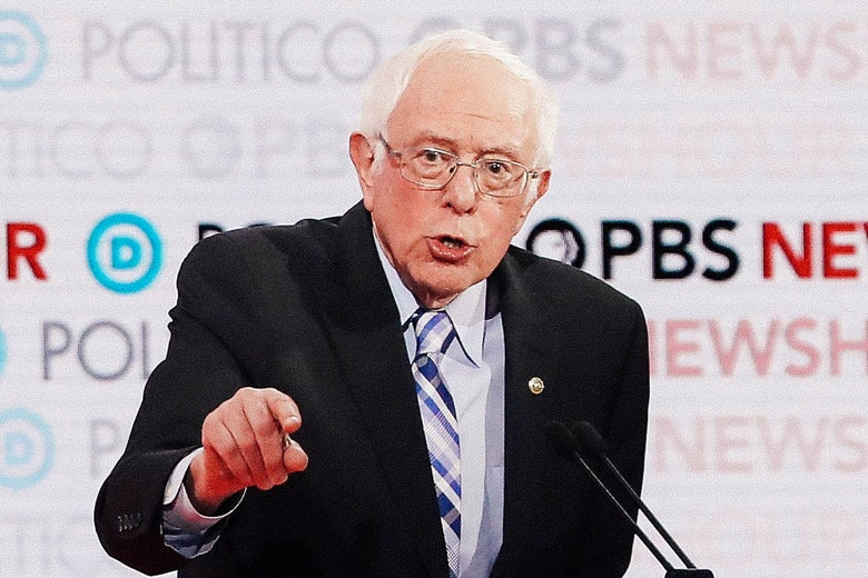 Bernie Sanders gestures while standing at a podium with a microphone. A screen says PBS NewHour and Politico behind him.