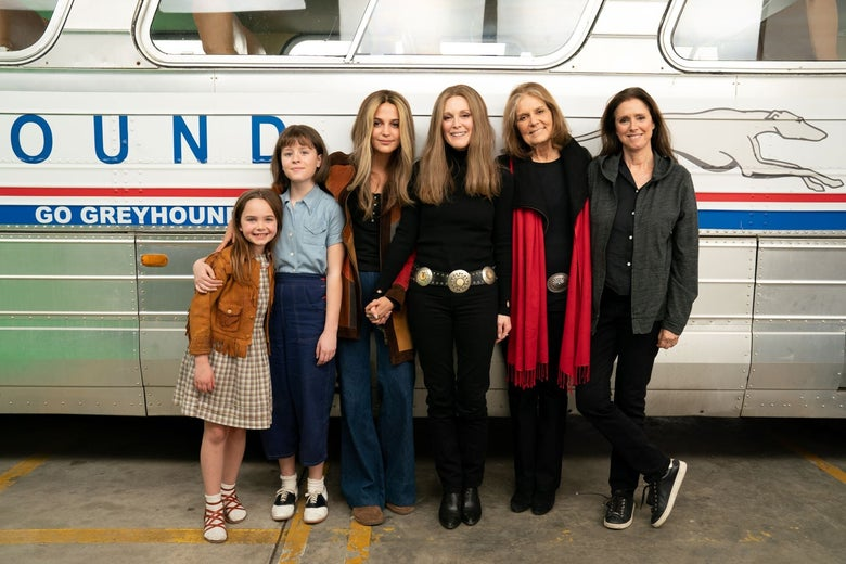 The six women stand in front of a Greyhound bus, many of them with long brown hair parted down the middle like Steinem's