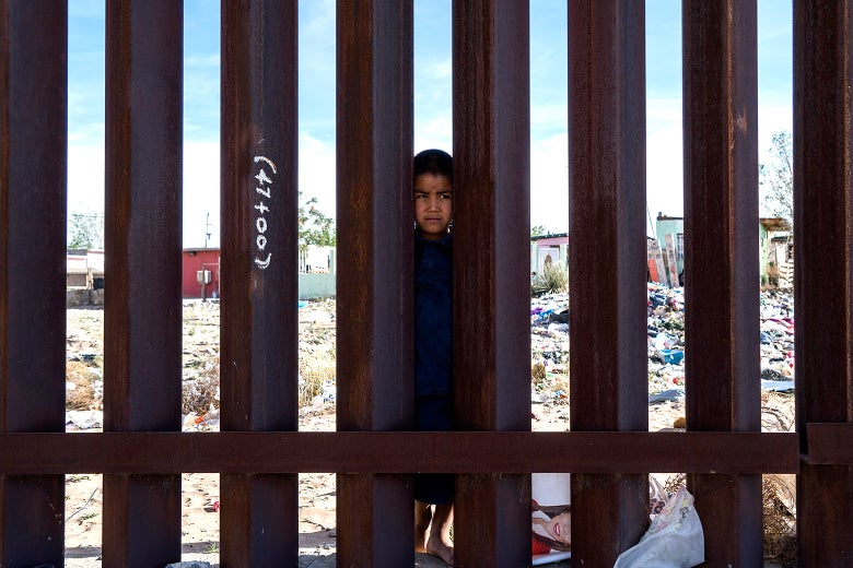 A young Mexican boy peers from the Mexican side of a border fence.