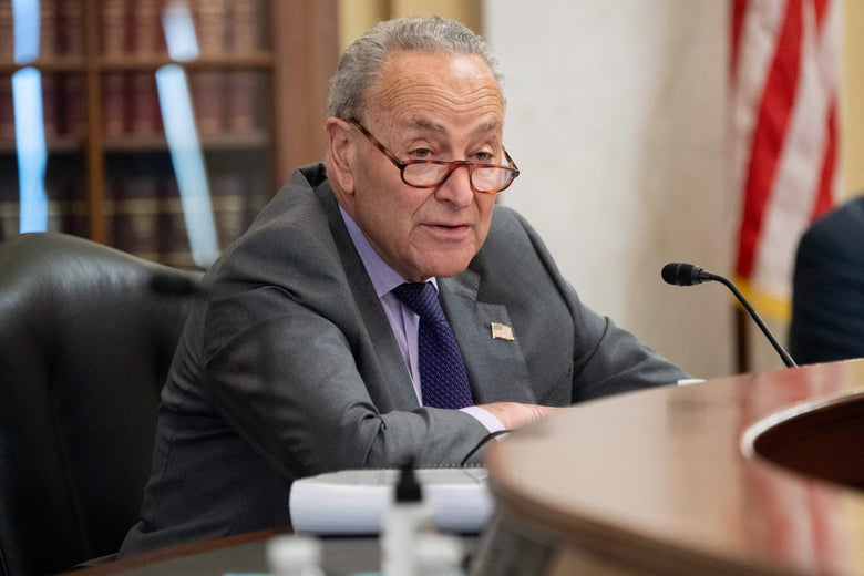 Schumer sits at a desk with a mic in front of him