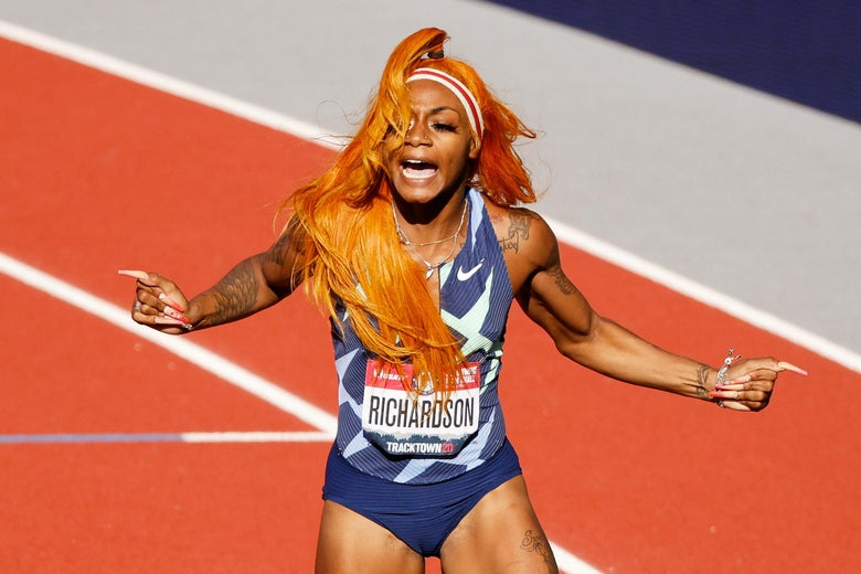 A woman with bright orange hair celebrates on a track.