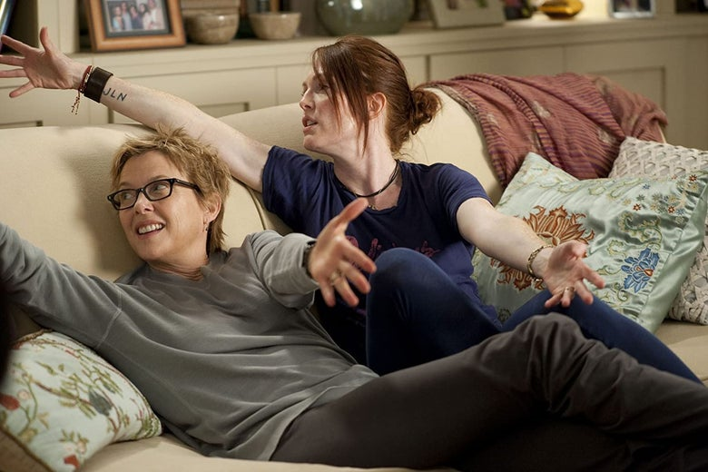 Annette Bening and Julianne Moore sit on a couch, looking offscreen with arms outstretched.
