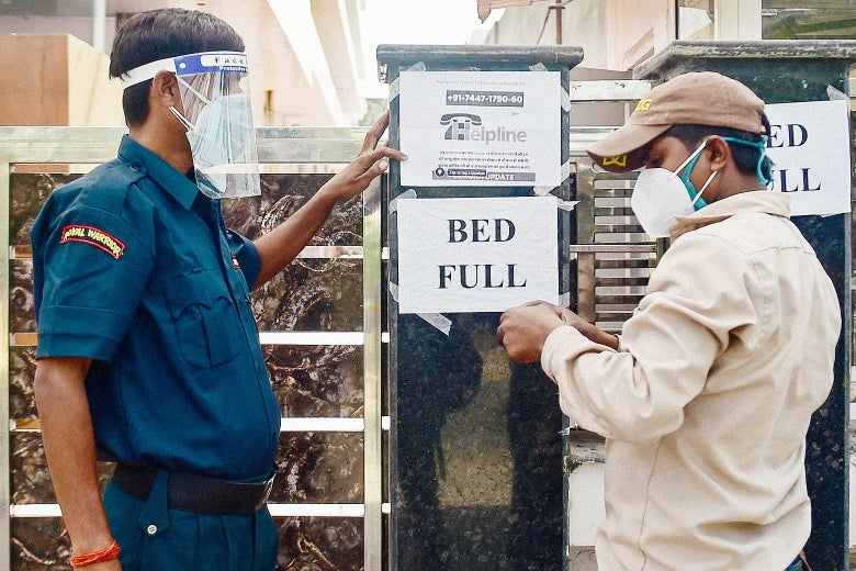 """Two men in masks tape up signs that say, """"BED FULL."""""""
