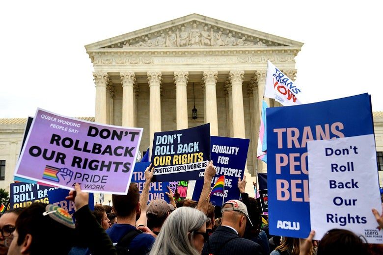 "LGBTQ rights activists protest outside the Supreme Court, holding signs that say ""Don't Roll Back Our Rights."""