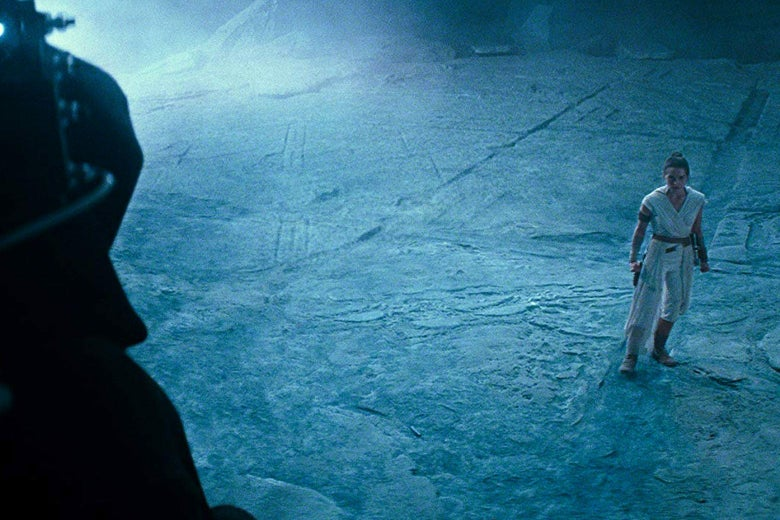 Daisy Ridley stands to the right of the image looking up at a dark, shadowy figure.