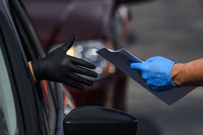 A gloved hand reaches out of a car window to collect unemployment forms from the gloved hand of a worker at a drive thru unemployment information center in Florida.