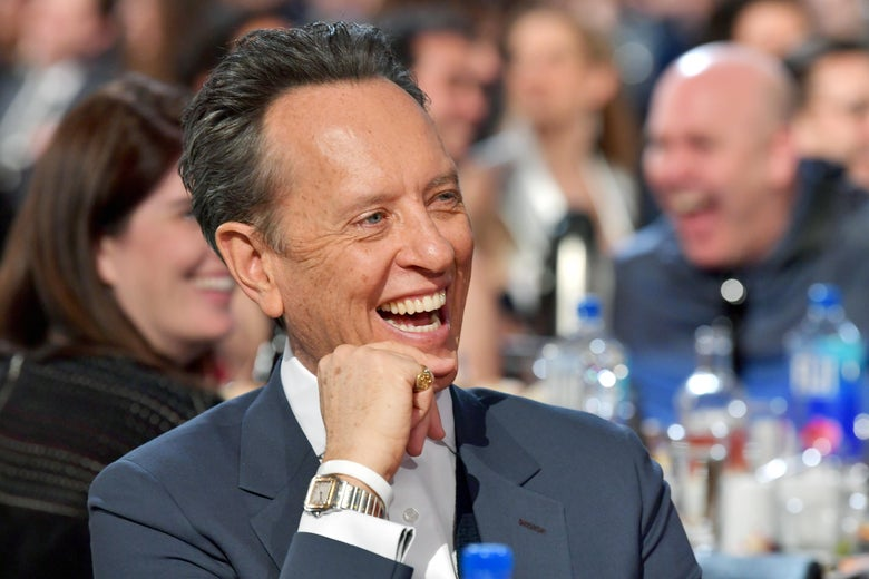 Richard E. Grant sitting at the Independent Spirit Awards, laughing.