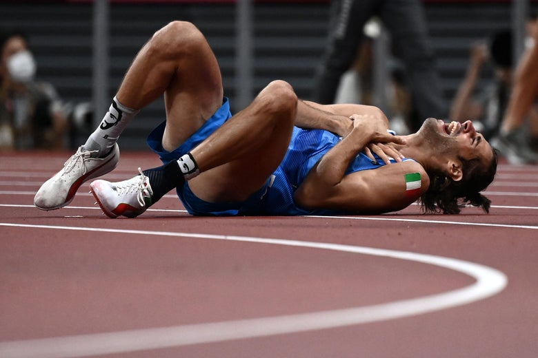 A high jumper lies on his back on the track, rolling on the ground, holding his hands to his heart, and screaming.