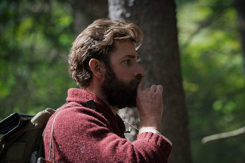 A bearded John Krasinski, seen in profile, holds a finger to his lips.