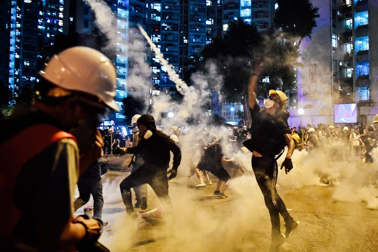 Protesters throw back tear gas fired by the police during a general strike in Hong Kong.