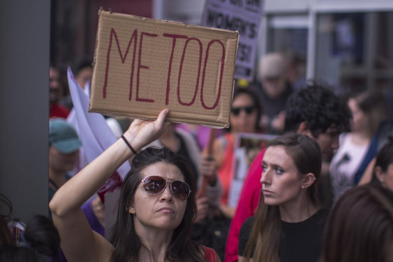 """A woman holds up a cardboard sign that says """"METOO."""""""