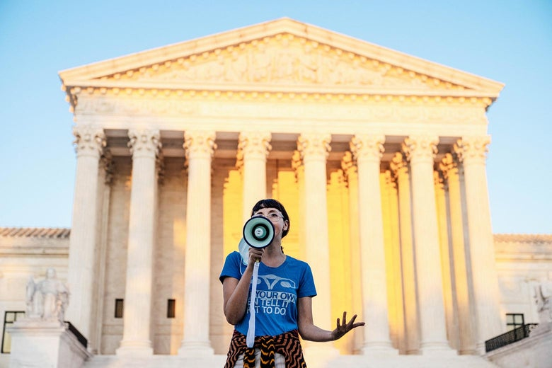 A protester speaks through a megaphone against a majestic view of the Supreme Court.