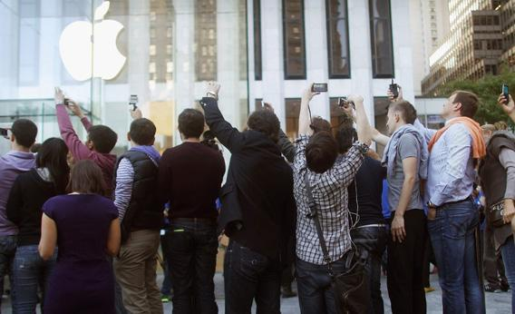 Customers take photos while in line to purchase iPhone 5.