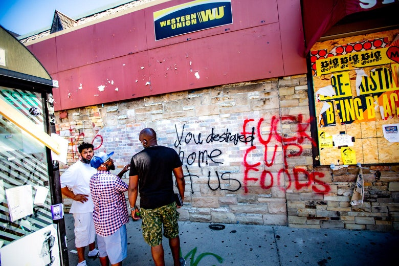 "Three men stand in front of a wall covered in graffiti, saying things like, ""FUCK CUP FOODS."""
